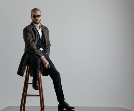 blond formal business man wearing a navy suit,coat,sunglasses sitting with one leg resting on a chair and one hand in pocket looking at camera serious on gray studio background