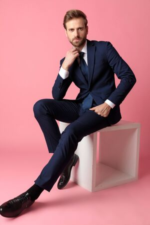 handsome formal business man in navy suit sitting with one hand resting on lap while fixing his collar with the other one and looking at camera serious on pink studio background