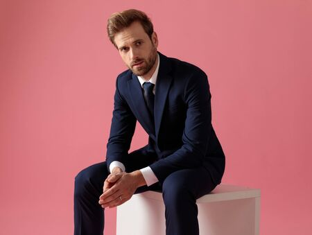 young formal business man in navy suit sitting and holding hands while looking at camera serious on pink studio background