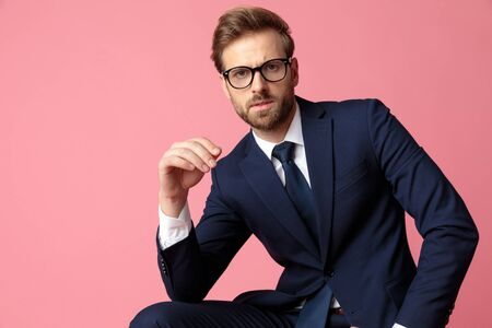 elegant formal business man in navy suit and glasses is sitting and resting his hands on his laps while  looking at camera serious on pink studio background