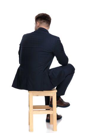 achteraanzicht van een jonge zakenman die naar de zijkant kijkt en denkt, zittend geïsoleerd op een witte achtergrond in de studio Stockfoto