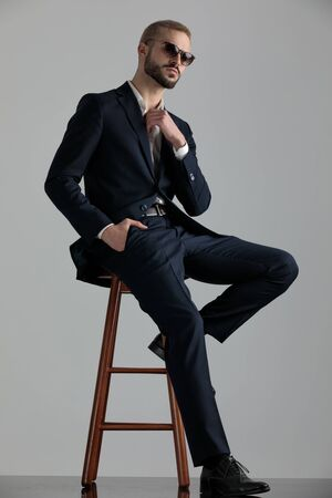 side view of a beautiful formal business man wearing a navy suit and sunglasses sitting with one leg resting on a chair and one hand in pocket fixing his shirts collar and looking at camera confident on gray studio background