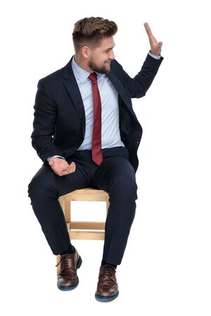 happy young businessman holding hands and saluting, sitting on white background in studio
