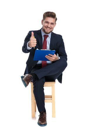 happy young businessman wearing holding clipboard and pen and making thumbs up sign, sitting isolated on wooden chair, on white background in studio