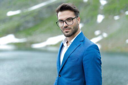 smart casual fashion model wearing blue coat, outdoor in nature at Balea Lake, Romania Stock Photo