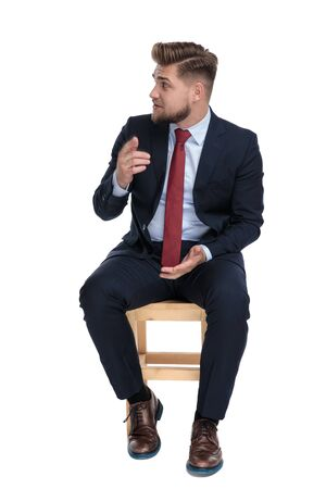 confused young businessman pointing finger and questioning, looking to side and sitting isolated on wooden chair, on white background in studio