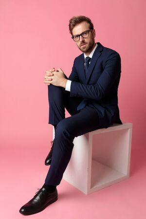 good looking formal business man wearing a navy suit and  glasses sitting and holding one leg resting on a chair and looking at camera serious on pink studio background