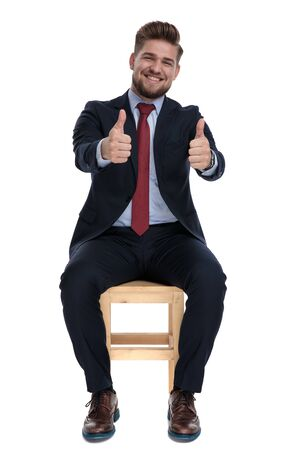 enthusiastic young businessman smiling and making thumbs up sign, sitting on white background in studio