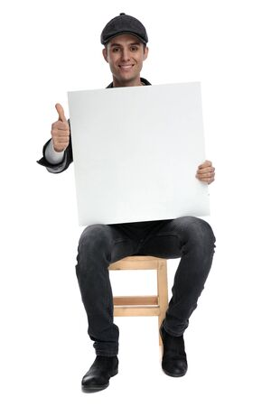 fine casual man with black leather jacket and hat sitting and holding a blank billboard while making a ok sign gesture on white studio background