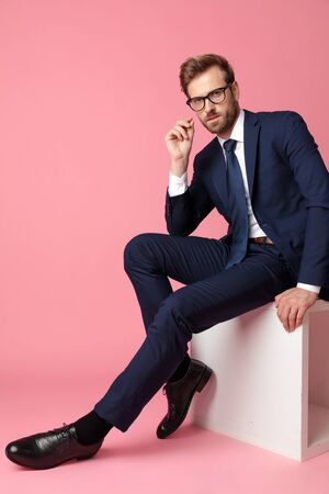 side view of a sexy formal business man in navy suit with glasses  sitting and resting one hand on his lap and the other on chair while looking at camera seductive on pink studio background