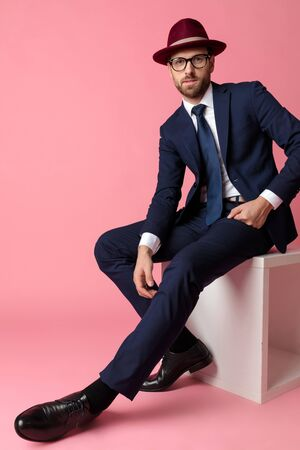 side view of a mysterious formal business man wearing a navy suit,glasses and burgundy hat  sitting and resting his hands on his laps while looking at camera happy on pink studio background Stock Photo