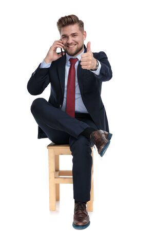 happy young businessman smiling, talking on the phone, making thumbs up sign and sitting isolated on white background in studio