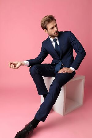 beautiful formal business man in navy suit is sitting and resting his hands on his laps with three fingers attached at one hand and looking away pensive on pink studio background