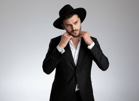 attractive young fashion model wearing tuxedo and black hat, fixing collar and looking to side, on grey background