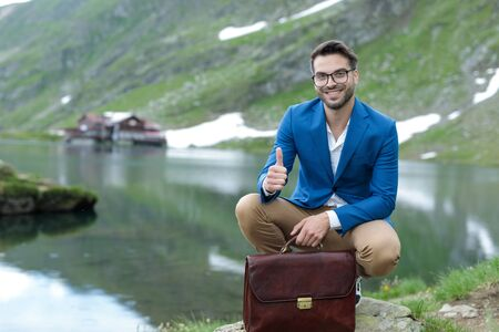 smart casual man wearing blue jacket, making thumbs up sign and smiling, holding suitcase, outdoor in nature at Balea Lake, Romania