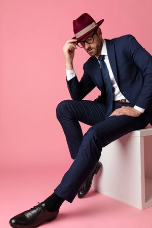 side view of a mysterious formal business man wearing a  navy suit,glasses,burgundy hat is sitting and resting his hands on his laps while fixing his hat and looking down serious on pink studio background
