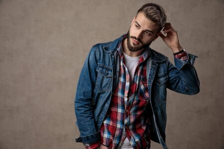 casual young fashion model wearing blue denim jacket, holding hand to head, thinking, standing on brown background in studio