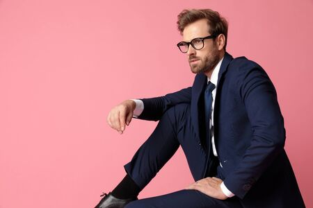 side view of a fine formal business man in navy suit with glasses  sitting and resting his hands on his laps and his leg on the chair while looking away pensive on pink studio background Stock Photo