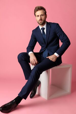 gorgeous formal business man in navy suit is sitting with hands resting on laps while looking at camera happy on pink studio background Stock Photo
