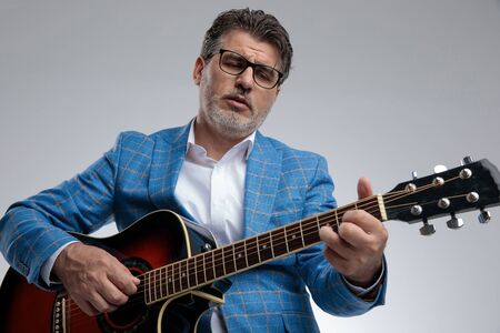portarit of a formal business man wearing light blue suit and eyeglasses sitting and playing his guitar while singing and looking down passionate against gray studio background