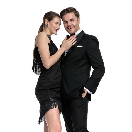Young couple smiling and laughing while he is holding his hand in his pocket and wearing a tuxedo, standing on white studio background