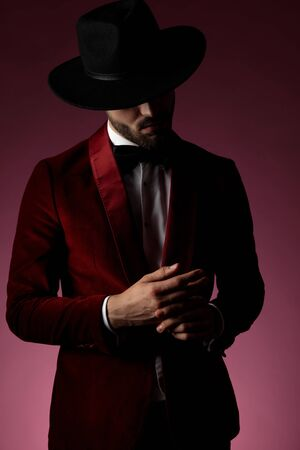 mysterious young fashion man wearing red velvet tuxedo and hat, touching fingers and looking down on pink background