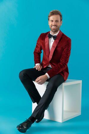 smiling fashion model wearing red velvet tuxedo, smiling and sitting on blue background in studio, full body 免版税图像
