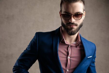 close up of a beautiful formal business man wearing a navy suit and sunglasses standing and looking at camera with a strong attitude against gray studio background Stock Photo