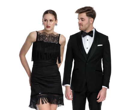 Unimpressed boyfriend wearing a tuxedo looking at his girlfriend while she is looking away and wearing a black dress, standing on white studio background