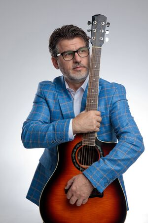 portrait of a gorgeous formal business man wearing a light blue suit and eyeglasses standing and holding his guitar tight while looking away pensive against gray studio background Imagens