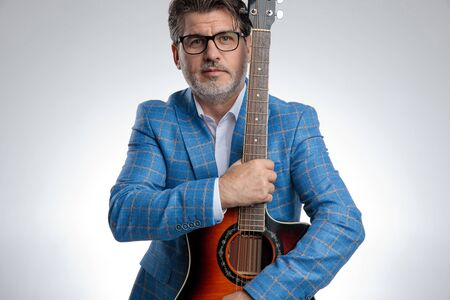 portrait of a charming formal business man wearing a light blue suit and eyeglasses standing and holding his guitar tight while looking at camera serious against gray studio background