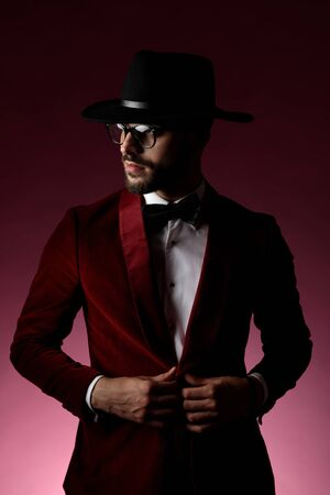 confident fashion model wearing red velvet tuxedo,black hat and glasses, arranging coat and looking to side, on pink background