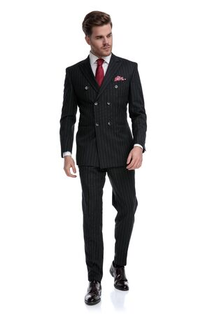 elegant young businessman wearing double breasted suit and red tie, looking to side and walking isolated on white background in studio