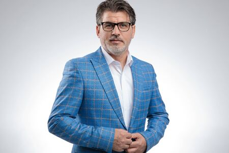 portrait of a beautiful formal business man wearing a light blue suit and eyeglasses standing and fixing his jacket while looking at camera confident against gray studio background