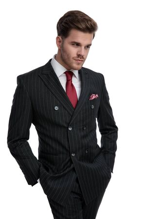 elegant businessman wearing double breasted suit and red tie, holding hands in pocket, looking to side, isolated on white background in studio Foto de archivo