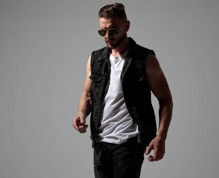 Thoughtful young man stepping forward while wearing sunglasses and a black jeans jacket on gray studio background
