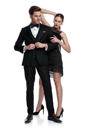 Confident couple posing while he is adjusting his jacket and looking away, she is standing behind him and holding her hand behind her head, wearing a tuxedo and black dress, standing on white studio background