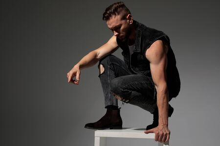 Handsome man squatting and getting off a chair while wearing a black jeans vest on gray studio background Stock fotó