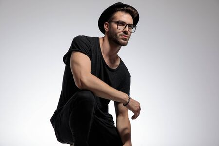 side view of a sexy casual man wearing shirt,hat,glasses standing crouched and looking away pensive against gray studio background