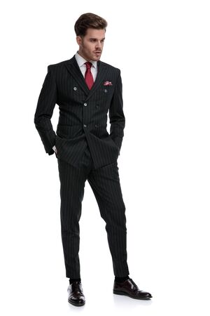 elegant businessman wearing double breasted suit and red tie, holding hands in pocket and looking to side, isolated on white background
