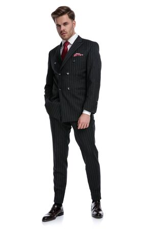 confident young businessman wearing double breasted suit,walking and holding hand in pocket, standing isolated on white background in studio