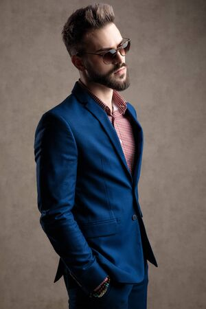 side view of a gorgeous formal business man wearing a navy suit and sunglasses standing with hands in pockets and looking ahead pensive against gray studio background