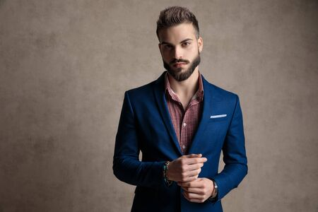 portrait of a sexy formal business man wearing a navy suit and holding hands while looking at camera confident against gray studio background