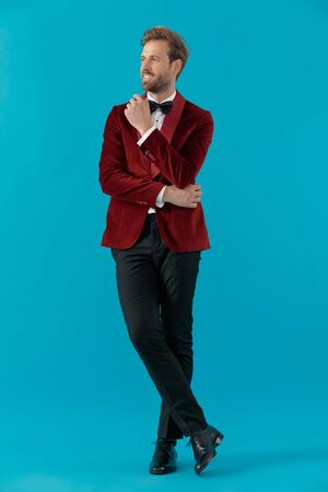 happy elegant man wearing red velvet tuxedo and smiling, holding hands and looking to side, standing on blue background, full body
