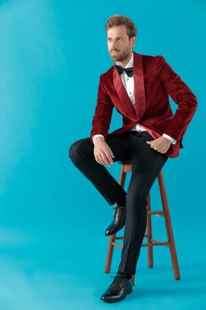 thoughtful elegant man wearing red velvet tuxedo, holding hands and looking to side, sitting on blue background, full body