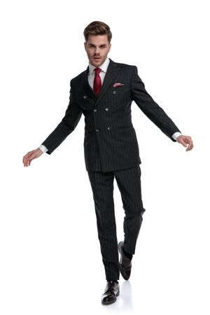 elegant businessman wearing double breasted suit and red tie, walking isolated on white background in studio Stock fotó
