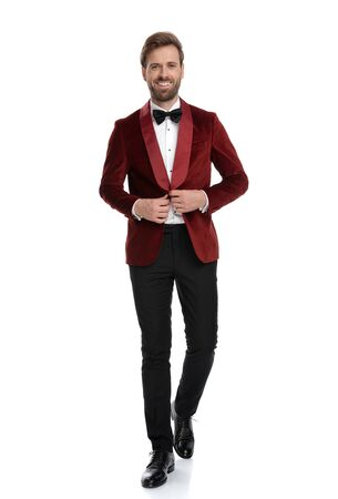 happy young fashion model wearing red velvet tuxedo, arranging coat and smiling, walking isolated on white background in studio Stock fotó