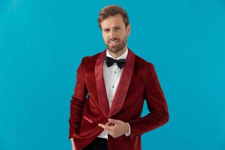 happy elegant man wearing red velvet tuxedo and pointing finger, holding hands and standing on blue background, full body