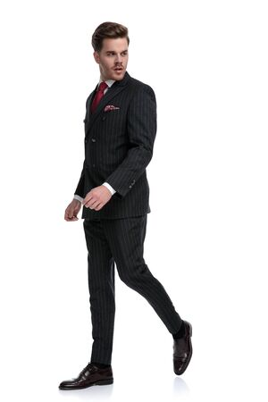 side view of elegant businessman wearing double breasted suit and red tie, looking to side, walking isolated on white background in studio