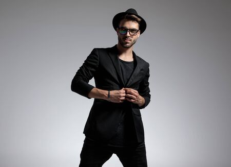 handsome casual man wearing hat and glasses standing and opening his jacket serious against gray studio background